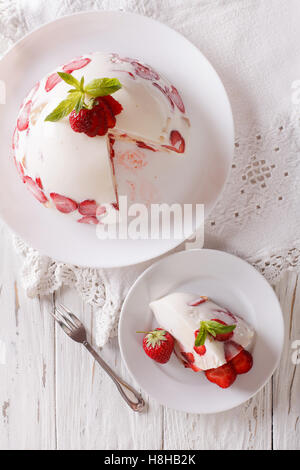 Cheesecake with fresh strawberries on a plate close up. vertical view from above - Stock Photo