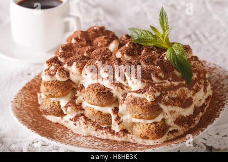 Tasty tiramisu on a plate and espresso coffee on a table close-up. Horizontal - Stock Photo