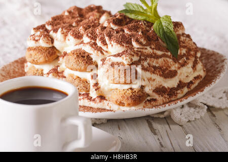 Italian Tiramisu cake on a plate and cup of black coffee on the table close-up. Horizontal - Stock Photo