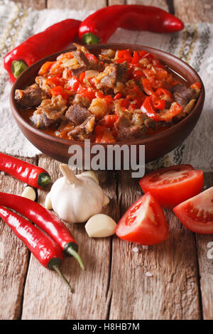 lamb stew with onions, tomatoes and pepper in a bowl close-up on the table. vertical - Stock Photo