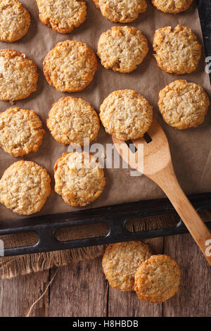 Anzac biscuits close up on a baking sheet on the table. vertical view from above - Stock Photo