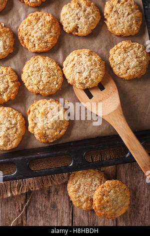 Anzac biscuits close up in baking dish on the table. vertical view from above - Stock Photo