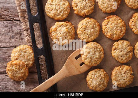 Anzac biscuits close up on a baking sheet on the table. horizontal view from above - Stock Photo