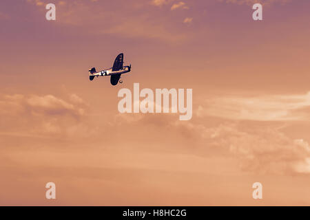Radio controlled toy airplane at sunset. RC model airplane flying in sunset. Airplane hobby. - Stock Photo
