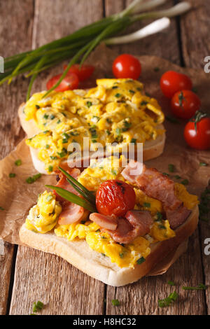 Homemade sandwich with scrambled eggs, bacon and tomatoes close-up on the table. Vertical - Stock Photo