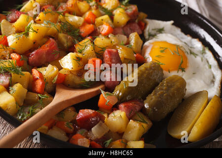 Scandinavian breakfast: pyttipanna with fried eggs and pickled cucumbers close-up on a plate. horizontal - Stock Photo