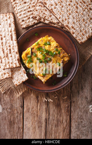 Matzah brei with green onions close-up on a plate. Vertical view from above - Stock Photo