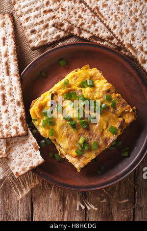 Jewish Breakfast: matzah brei with green onions close-up on a plate. Vertical view from above - Stock Photo