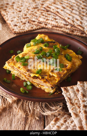 Jewish cuisine: matzah brei with green onions close-up on a plate. Vertical - Stock Photo