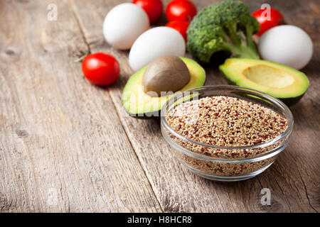 Ingredients for making a healthy breakfast. Quinoa with fresh vegetables: avocado, tomatoes, broccoli, eggs on  - Stock Photo