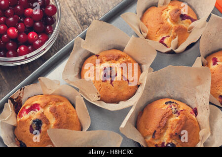muffins with cranberries, cranberries in a glass bowl on the old wooden background - Stock Photo