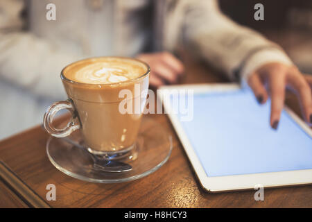 Woman using tablet in restaurant while on coffee break - Stock Photo