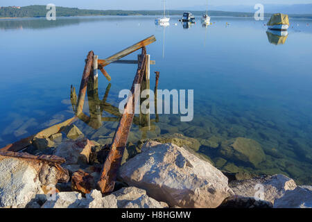 Tranquill scene of bay in the morning with an old, rusty pier in foreground and anchored boats in background - Stock Photo