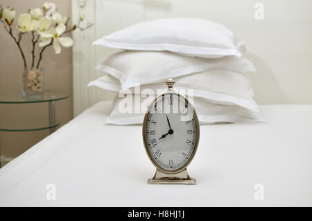 Alarm clock showing five to eight on a bed with pillows in background - Stock Photo