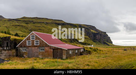 Farm house nestled into the mountainside in South Iceland - Stock Photo