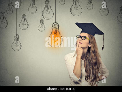 Closeup portrait beautiful thoughtful graduate student girl young woman in cap gown looking up at bright light bulb - Stock Photo