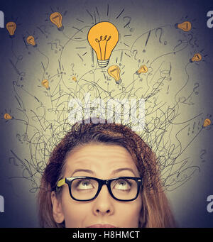 Closeup thinking woman with question signs and light idea bulb above head looking up on gray wall background - Stock Photo