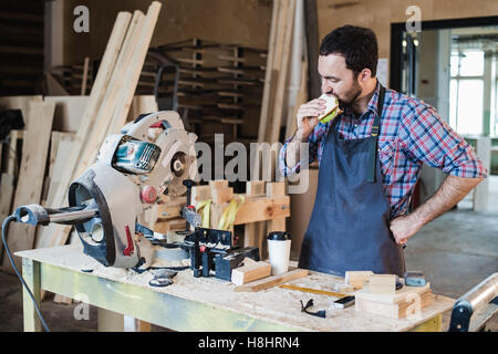Cheerful carpentry worker having lunch eating sandwich in a workshop - Stock Photo