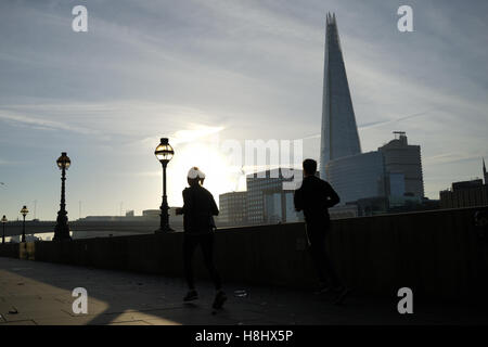 A couple running along the Thames river, London - Stock Photo