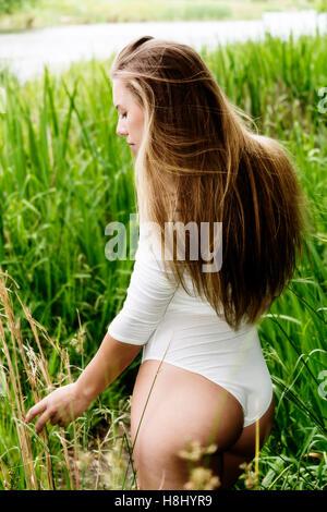 Caucasian Teen Girl Standing In White Leotard Amid Green Grass Near River - Stock Photo