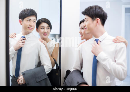 Young Chinese couple looking into a mirror before going to work - Stock Photo