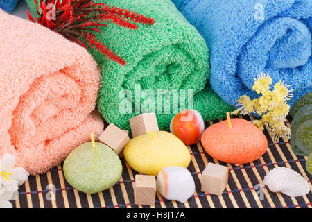 Colorful rolled towels with flowers, candles and stones closeup picture. - Stock Photo