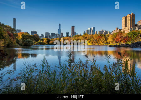 Fall in Central Park at The Lake with Midtown and Upper West Side skyscrapers. Autumn foliage in New York City - Stock Photo