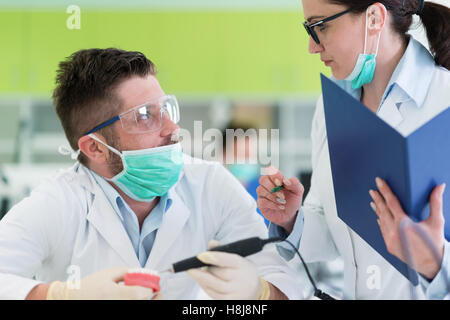 Busy young stomatology students working carefully on anatomical models - Stock Photo