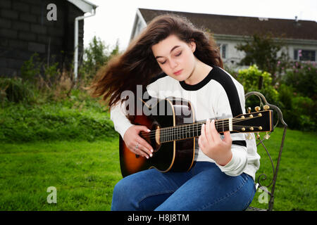Teenage girl playing an acoustic guitar outside - Stock Photo