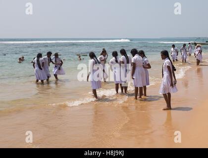 Schoolchildren playing on a beach in Sri Lanka - Stock Photo