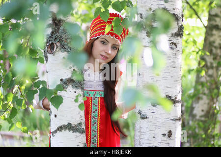 Slav in traditional dress hiding behind trees - Stock Photo