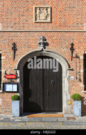 Entrance door of the former Guildhall of the Tanners (1630), currently a restaurant, in Bruges, Belgium - Stock Photo