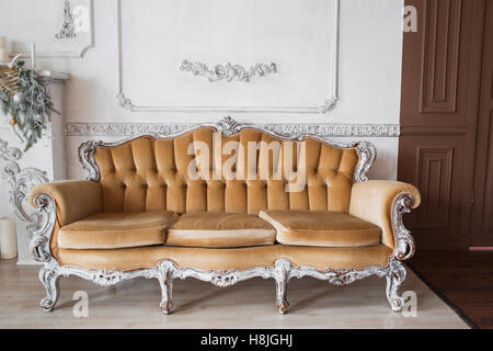 Living room with antique stylish beige sofa on luxury white wall design bas-relief stucco mouldings roccoco elements. - Stock Photo