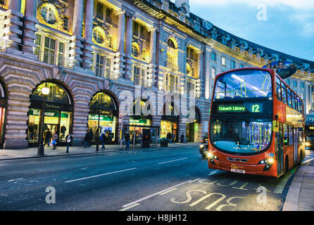 Traditional red bus in a street at dusk. - Stock Photo
