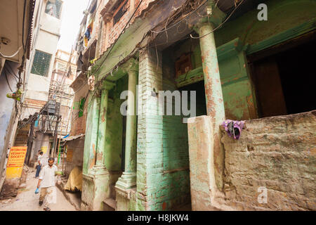 VARANASI, INDIA - 26 Oct 2016: Man walks down back alleyways on October 26, 2016 in Varanasi, India - Stock Photo