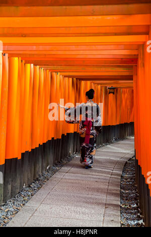 KYOTO, JAPAN - OCTOBER 8, 2016: Unidentified woman at walkway in Fushimi Inari shrine in Kyoto, Japan. This popular - Stock Photo