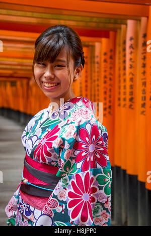 Unidentified woman at walkway in Fushimi Inari shrine in Kyoto, Japan. - Stock Photo