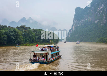 Boat cruise on Li river surrounded by famous karst landscape on misty and foggy day - Stock Photo