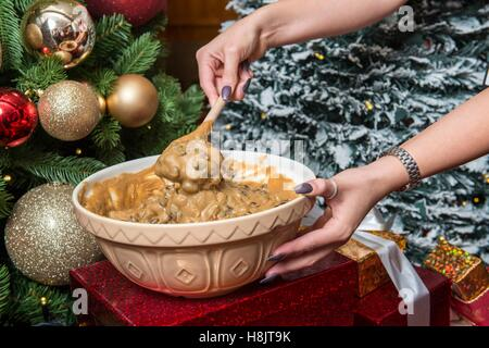 Traditional Christmas Pudding mixture being mixed in a ceramic bowl in preparation for being cooked in an oven - Stock Photo