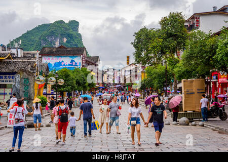 View over downtown of Yangshuo with people on the street and recognizable karst peaks in the background - Stock Photo