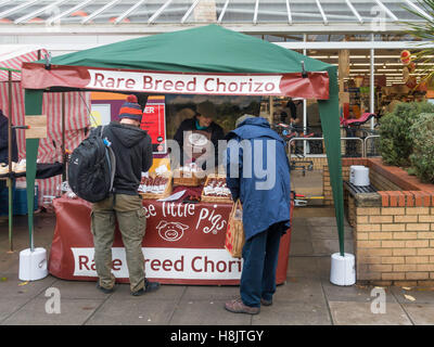 A woman stall holder at a UK farmer's market serving Three Little Pigs brand rare breed Chorizo Spanish style sausages - Stock Photo
