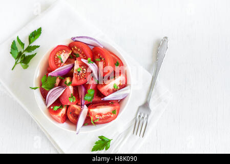 Tomato salad with onion, parsley and black pepper in bowl - healthy vegetarian vegan food appetizer - Stock Photo
