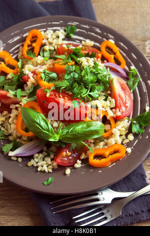 Fresh organic tomato and couscous salad with vegetables and greens - healthy vegetarian salad on rustic plate close - Stock Photo