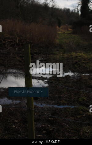 private property barbed wire fence in front of muddy puddles - Stock Photo