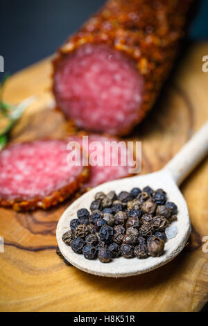 dried salami crusted in ground red pepper on dark background - Stock Photo