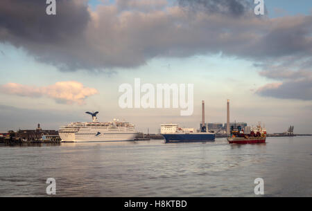 two ships on river thames passing the moored cruise ship cmv magellan as seen from gravesend pier - Stock Photo