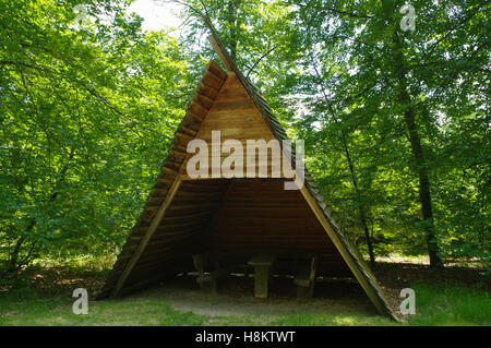 a table and bench in wooden bower in resting place in a forest - Stock Photo