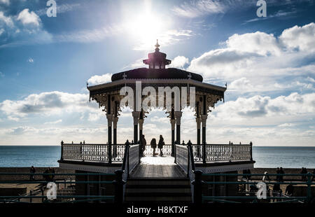 People silhouetted on The Bandstand, Hove, on the seafront. The bandstand is a fine example of Victorian architecture. - Stock Photo