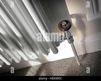 Close view on retro style white domestic radiator with wooden temperature control valve in luxury home setting - Stock Photo