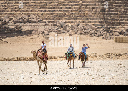 Cairo, Egypt Camel drivers on horseback and a tourist riding a camel walking through the desert with the Great Pyramids - Stock Photo